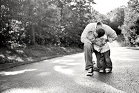 black and white image of dad kissing his toddler son on the cheek
