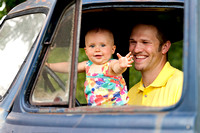 little girl waving with dad in blue truck