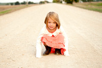 little girl wearing coral dress sitting on country road